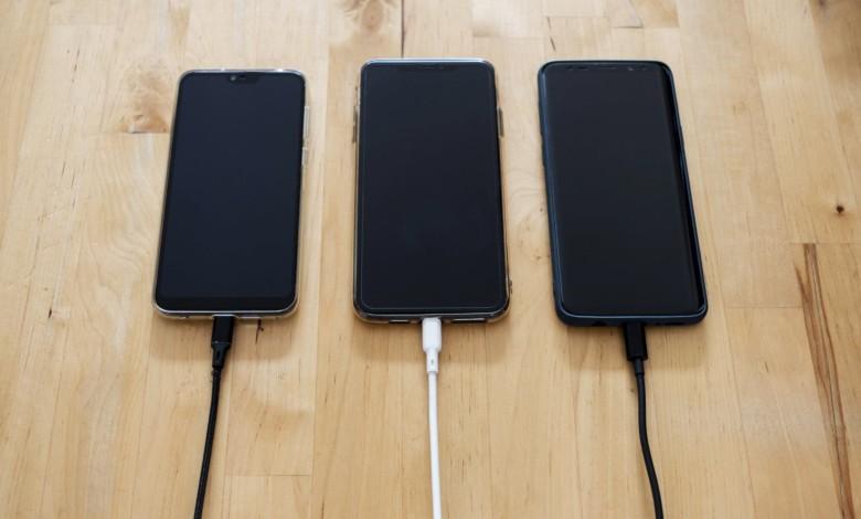 3 smartfony podłączone do ładowarek na biurku